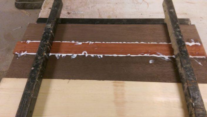Collage padouk, noyer et pin pour table sur mesure en bois massif