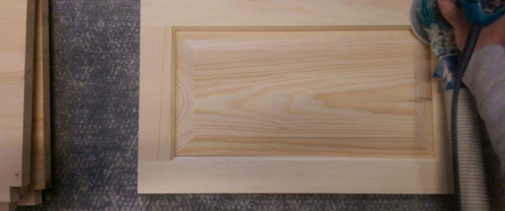 Sablage d'une porte de cuisine pour des armoires de cuisine en pin massif